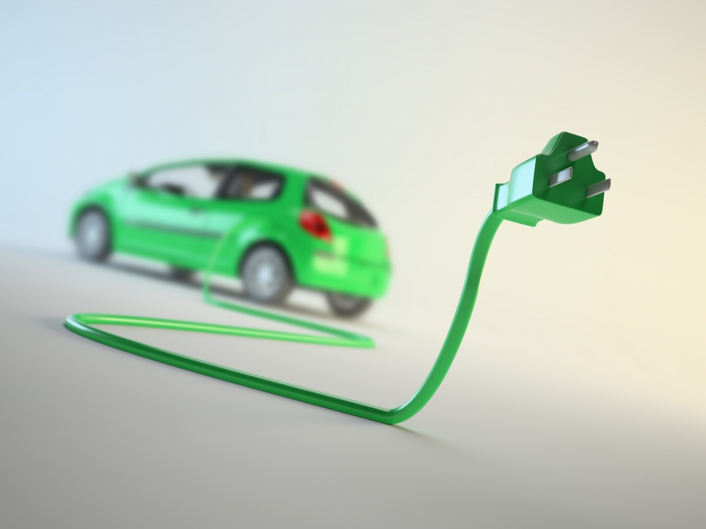 An electric car connected to a plug - EV transport concept
