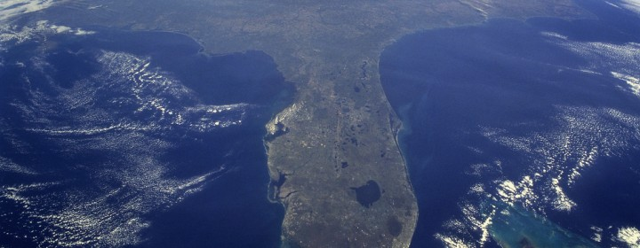 "Taken during the STS-95 mission from a point over Cuba, this photo shows an oblique, foreshortened view of the Florida Peninsula, with the light blue, shallow seafloor of both the Florida Keys (curving across the bottom of the view) and the Bahama banks (right). ""Popcorn"" cumulus cloud covers Miami and the Southern Everglades, although the built-up area from Ft. Lauderdale to West Palm Beach can be discerned. Lake Okeechobee is the prominent waterbody in Florida. Cape Canaveral is shown well, half way up the peninsula. Orlando appears as the lighter patch West (left) of Cape Canaveral, near the middle of the peninsula. Cape Hatteras appears top right, with the North part of Chesapeake Bay also visible. This is a visibility of 16 degrees of latitude (23 degrees N over Cuba to 39 degrees at Baltimore), showing unusual atmospheric clarity.  Credit: NASA"